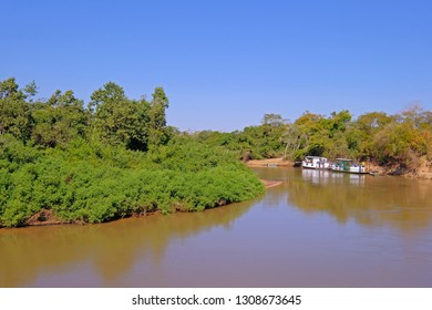 Densely forested shores of the Aquidauana river in the brazilian Pantanal, houseboats on the riverbank, Aquidauana, Mato Grosso Do Sul, Brazil, South America