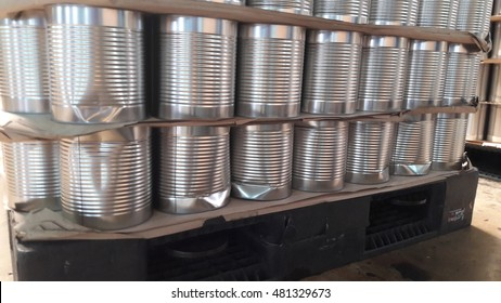 Dent canned food stacking on wooden pallet with paper sheets