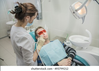 dental care concept stomatology inspection. the patient lies in a chair in dentistry in front of him a hand with drill. the dentist is in the office beside the chair with the patient