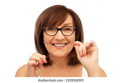 dental care and hygiene people concept - portrait of smiling senior woman cleaning her teeth by floss over white background