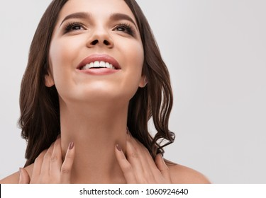 Dental care, oral health, stomatology, skin care, treatment concept. Woman smile. Beauty girl face. Model with strong white teeth. Holding hands near the shoulders and neck. Looking up, happy look.
