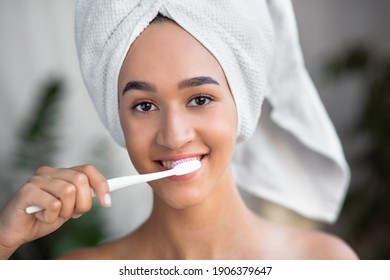 Dental care, oral hygiene, healthy teeth, daily procedure. Attractive smiling young african american woman in towel after shower cleans teeth with toothbrush in interior of bath in morning, close up