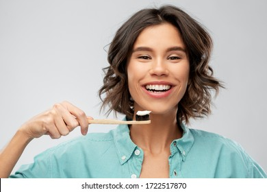 dental care, oral hygiene and people concept - portrait of happy smiling young woman in turquoise shirt with toothpaste on wooden toothbrush over gray background