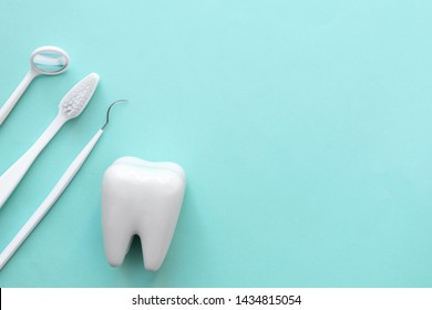 Dental care set, tooth model with toothbrush, dental explorer probe and dentist mirror on green background with copy space.