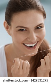 Dental care. Smiling woman cleaning white teeth with floss. Portrait of girl with beautiful smile flossing teeth for oral hygiene and tooth health