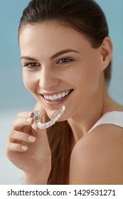 Dental care. Smiling woman with healthy teeth using removable clear braces aligner, orthodontic silicone trainer. Portrait girl with white smile using invisible whitening tray