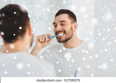 dental care , winter, christmas people and hygiene concept - smiling young man with toothbrush cleaning teeth and looking to mirror at home bathroom over snow