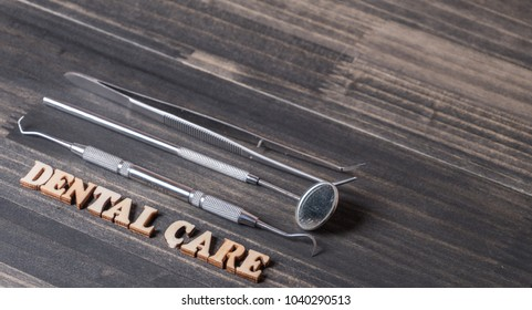 'Dental Care' words with dental tools on dark wooden background