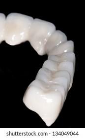 Dental ceramic bridge in black background and its reflection image