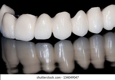 Dental ceramic bridge in black background and its reflection image