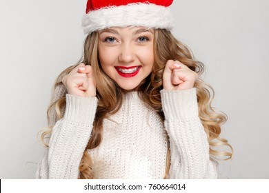 dental, christmas, xmas, winter, happiness concept - smiling woman in santa helper hat, Beautiful female model wear santa hat. girl with braces, dentistry