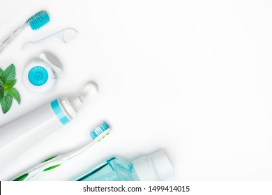 Dental cleaning tools and hygiene products on white with copyspace