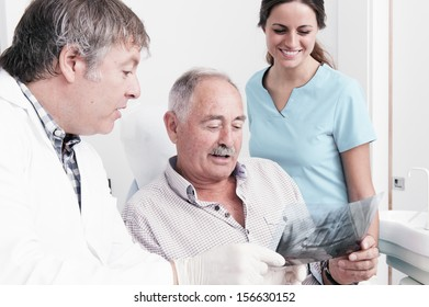 Dental Clinic. An elderly retired gentleman, discussing with his dentist radiography (x-ray) results