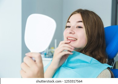 Dental clinic. Reception, examination of the patient. Teeth care. Young girl smiling, looking in the mirror after a dental checkup at her dentist