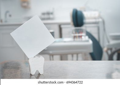 Dental clinic, tooth holding blank card, dentistry.