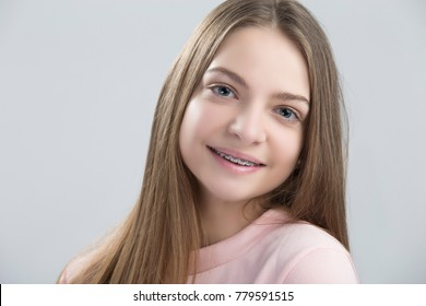 Dental Concepts. Portrait of Happy Teenage Female With Teeth Brackets. Posing Half Turned with Smile Against White.Horizontal Image