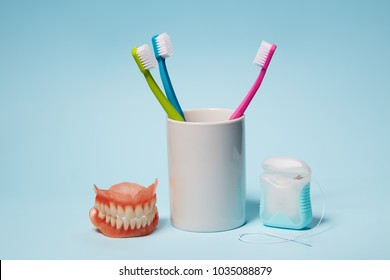 Dental Equipment. Colorful toothbrushes, dentures and dental floss on light blue background.