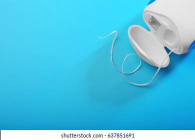 Dental floss on color background