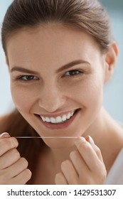Dental floss. Smiling woman cleaning white teeth with floss. Portrait of girl with beautiful smile flossing teeth for oral hygiene and tooth health care