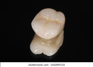 A dental full milled zirconia porcelain crown of a molar tooth in dark background