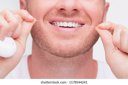 Dental Health Care Concept. Healthy White Teeth. Closeup Portrait Of Handsome Happy Smiling Man With Fresh Perfect Smile.  Young Man Cleaning Teeth With Dental Floss.