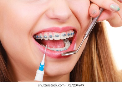 Dental health care, stomatology concept. Woman with braces having dentist appointment, looking at teeth with small mirror and cleaning using tiny toothbrush.