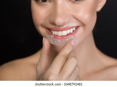 Dental health concept. Close up of female mouth is wearing clear aligner on teeth for orthodontic correction of bite. Selective focus