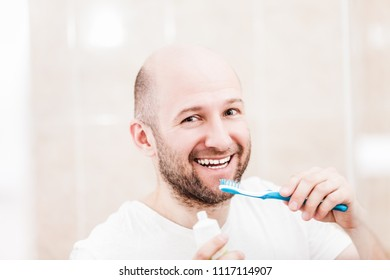 Dental hygiene - adult caucasian bald man hand holding toothbrush with toothpaste and brushing teeth