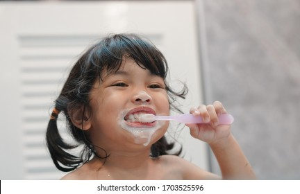Dental hygiene. Asian cute  child girl or kid brushing her teeth by toothbrush in the bathroom. Healthcare concept.