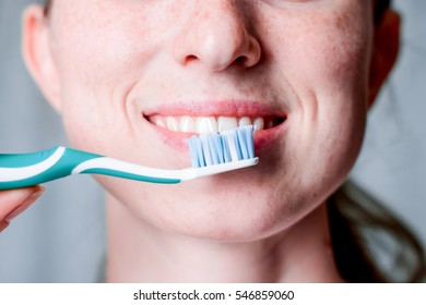 Dental hygiene and care. White toothbrush. Young healthy woman face with beauty smile. Tooth brush. Oral clean, whitening. Beautiful girl. Person healthcare. Female in the morning in bathroom.