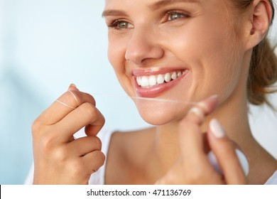 Dental Hygiene. Closeup Of Beautiful Happy Smiling Woman With Beauty Face And Perfect Smile Cleaning, Flossing Healthy White Teeth Using Floss. Oral Health, Tooth Care Concept. High Resolution Image