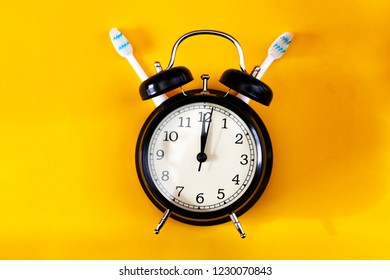Dental hygiene concept. Black alarm clock with two toothbrushes and yellow background.