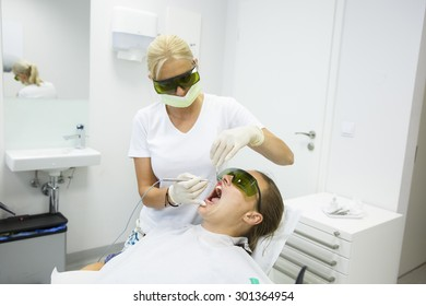 Dental hygienist using a modern diode dental laser for periodontal care, wearing protective glasses, preventing eyesight damage. Periodontitis, dental hygiene, preventive procedures concept.