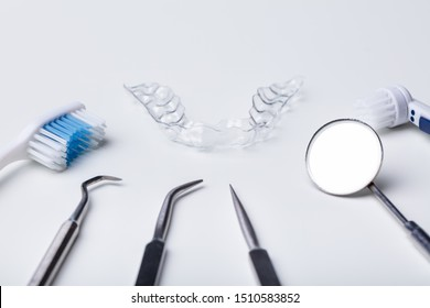 Dental Instruments And Clear Aligner On White Background