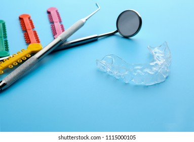 Dental instruments and occlusal splint on color background