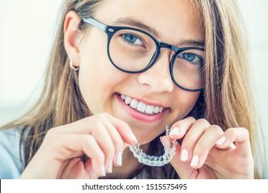 Zahnliche unsichtbare Klammern oder Silikon-Trainer in den Händen eines jungen lächelnden Mädchens. Orthodontisches Konzept - Invisalign.