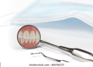 Dental mirror displays image of clenched front teeth beside metal pick and mask on white table