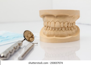 Dental mold showing the teeth of the upper and lower jaw with dental tools and a face mask on a wooden table in a dental care and examination concept
