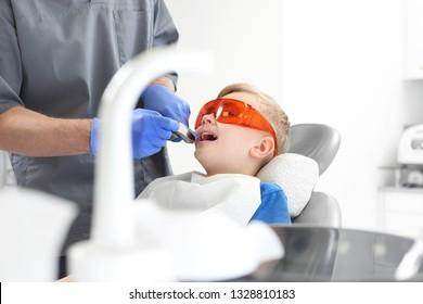 A dental office, a child in a dental chair. A child in a dental chair during a dental treatment.