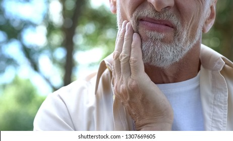 Dental pain, retired man suffering from toothache, teeth prosthetics, dentistry