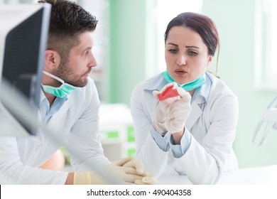 Dental prosthesis, dentures, prosthetics work. Dental students while working on the denture, false teeth, a study and a table with dental tools.