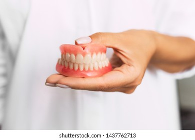 Dental prosthesis in the hands of the doctor close-up. Dentist holding ceramic dental bridge. Front view of complete denture. Dentistry conceptual photo. Prosthetic dentistry. False teeth