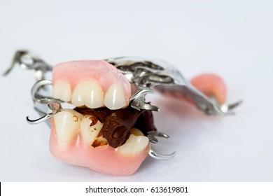 Dental prosthetics (denture) and chocolates on a white background