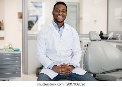 Dental Services. Professional Black Male Stomatologist Posing At Workplace In Clinic Interior, Happy African American Dentist Dentist Doctor In Uniform Smiling At Camera, Ready For Check Up