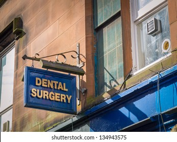 "Dental surgery office: a new small business sign with ""DENTAL SURGERY"" spelled in bold, golden letters"