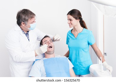 Dental surgery. There is a dentist, his assistant and the patient