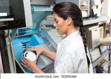 Dental technician puts ceramics implant in a milling machine