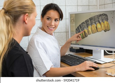 Dental technician showing patient a scan of prosthesis on computer screen