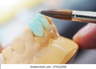 dental technician working on false teeth. table with dental tools.
