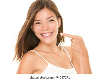 Dental teeth - perfect smile woman pointing at toothy smile looking happy at camera. Dental teeth concept photo with mixed race asian caucasian female model isolated on white background.